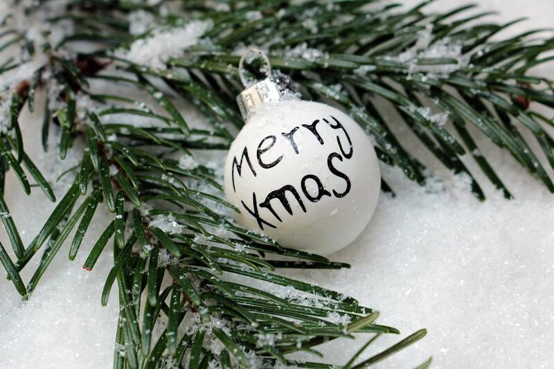 Witte kerstbal met dennentak en sneeuw